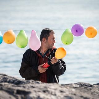 Хозяин тира надувает шарики-мишени на берегу моря, Кадыкёй  Shooting range keeper blows balloons used as targets, Kadiköy neighbourhood
