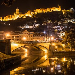 Ночной вид центра Тбилиси с Метехским мостом, частью старого города и возвышающейся над ним крепостью Нарикала A night view over the centre of Tbilisi with Metekhi bridge, part of the Old Town and Narikala fortress towering over it