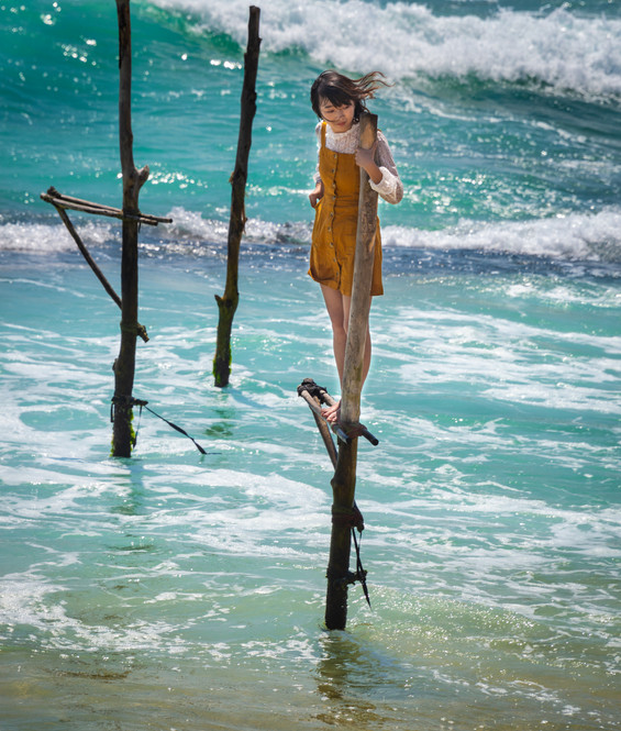 Туристка позирует на шесте для ловли рыбы, Ахангама  A tourist poses on a fisherman stilt, Ahangama