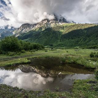 Накрытая облаками Ушба и ее отражение в луже Cloud-covered Ushba mountain and its reflection in a puddle