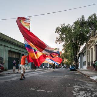 """Конец января – время подготовки к карнавалу в Монтевидео: кандомбе на улицах района Палермо. Кандомбе – традиционный уругвайский стиль музыки и танца, берущий начало в музыкальных и танцевальных традициях завезенных из Африки рабов. Несмотря на то, что в Уругвае африканских рабов было не очень много, традиция прижилась настолько хорошо, что стала основным мотивом ежегодного карнавала в Монтевидео, и признана ЮНЕСКО в качестве всемирного культурного наследия. Считается, что кандомбе стал массово популярен в стране в конце 19 века, когда черные сообщества Уругвая переключились на европейские танцы, а вот среди белого большинства неожиданно стала популярной именно африканская музыка и африканские танцевальные шествия. Музыка кандомбе – это ритмы, исполняемые на барабанах трех различных видов. Обычно шествия кандомбе можно видеть в Монтевидео, особенно в районах Палермо и Баррио-Сур, по воскресеньям, на некоторые праздники (в канун Нового года, в Рождество и в дни некоторых святых), но самый """"разгул"""" происходит в выходные в последние недели перед февральским карнавалом: вечерами по улицам ходит часто сразу несколько шествий (представляющие разные группы, называемые """"компарса""""), каждая компарса отличается цветами одежд и барабанов, флагами. Общее заключается в составе шествия, ритмах и танцевальных движениях. Обычно шествие возглавляют знаменосцы, за ними идет танцевальная группа из девушек (здесь виден ее """"хвост""""), затем один или несколько """"специальных персонажей"""", изображающих либо героев африканских мифов, либо белых рабовладельцев из старых колониальных времен, а потом уже идут барабанщики. Эти парады по улицам района Палермо – репетиции перед главным карнавальным представлением, поэтому участники на фотографии одеты во что попало.   Candombe parade in the streets of Palermo neighbourhood, Montevideo, in the end of January: a rehearsal to February's carnival performance. Candombe is Uruguayan music and dance that comes from African slaves. It is considered an importa"""