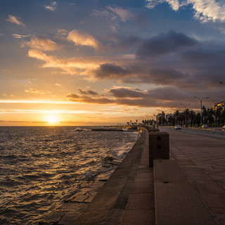 Ветренный вечер и закат над набережной Рамбла, Монтевидео, Уругвай. Несмотря на совершенно морские виды, столица Уругвая стоит на берегу не моря и не океана (хотя океан недалеко), а реки Ла-Плата, правда, река здесь имеет ширину более 50 километров, хотя вода все же пресная. А набережная Рамбла, тянущаяся вдоль всего города – одна из самых длинных (если не самая) в мире – более 20 километров, хотя, на самом деле, на карте города Рамбла разделена на почти пару десятков отрезков, имеющих свои собственные имена (Rambla Sudamerica, Rambla F.D. Roosevelt, Rambla Gran Bretaña, Rambla Mahatma Gandhi и так далее); тем не менее, это фактически единая набережная с единым оформлением. Обычно тут всегда много народу (хотя понятие «много народу» в Монтевидео сильно отличается от Москвы) – ездящих на великах и на роликах, занимающихся на тренажерах, которые разбросаны по набережной, ловящих рыбу, просто сидящих на парапете или на принесенных раскладных креслах и, разумеется, пьющих мате. Влюбленные и одинокие, молодые и пожилые – все тусят на Рамбле. Так что в кадре - редкий момент, когда в видимости ни души, а только пейзаж с закатом.  Windy day's sunset over Rambla, Montevideo's more than 20 kilometres long embankment which stretches along entire city, bordering on La Plata river – with the width of more than 50 km La Plata looks here like the sea or Atlantic Ocean itself – but actually it's still a river)