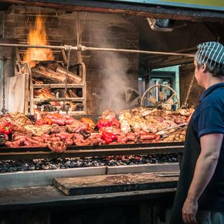 "Жареное мясо, 'асадо' - главное блюдо в уругвайском меню. Мясо здесь готовят необыкновенно вкусно, это целое искусство. Помимо встречающихся на каждом шагу заведений, специализирующихся на жарке мяса - называемых ""паррилья"" (а в уругвайском произношении - ""парриша""), часто уругвайцы жарят мясо прямо на улицах.  'Asado' which is Spanish word for barbecued meat, is the main dish of Uruguayan menu. Grilling meat is a kind of art in Uruguay, always giving wonderfully tasty results. 'Parrillas' – meat grilling restaurants, could be spotted everywhere, and often Uruguayans make grilled meat right in the streets or in courtyards."