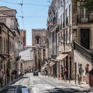 Вид вдоль улицы Аугушту Розас башнями лиссабонского кафедрального собора на заднем плане A view down Augusto Rosa street with the towers of Lisbon Cathedral in the background