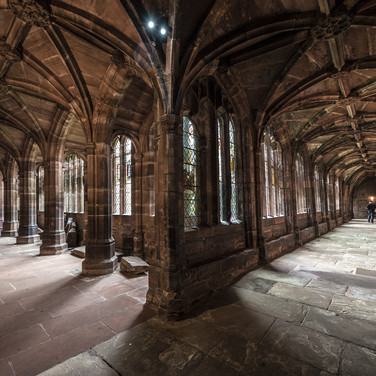 Сводчатая галерея с витражными окнами окружает клуатр собора в Честере Arched gallery with stained-glass windows encircled cathedral cloister in Chester