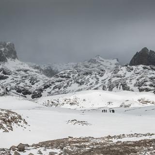 Лыжники на заснеженном плато в горах Пикос-де-Эуропа A group of skiers moves across snowy plateau in Picos de Europa mountains