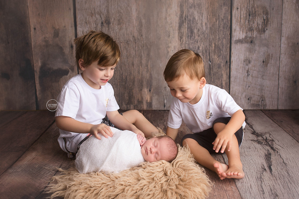 newborn baby with big brothers on rustic wood backdrop