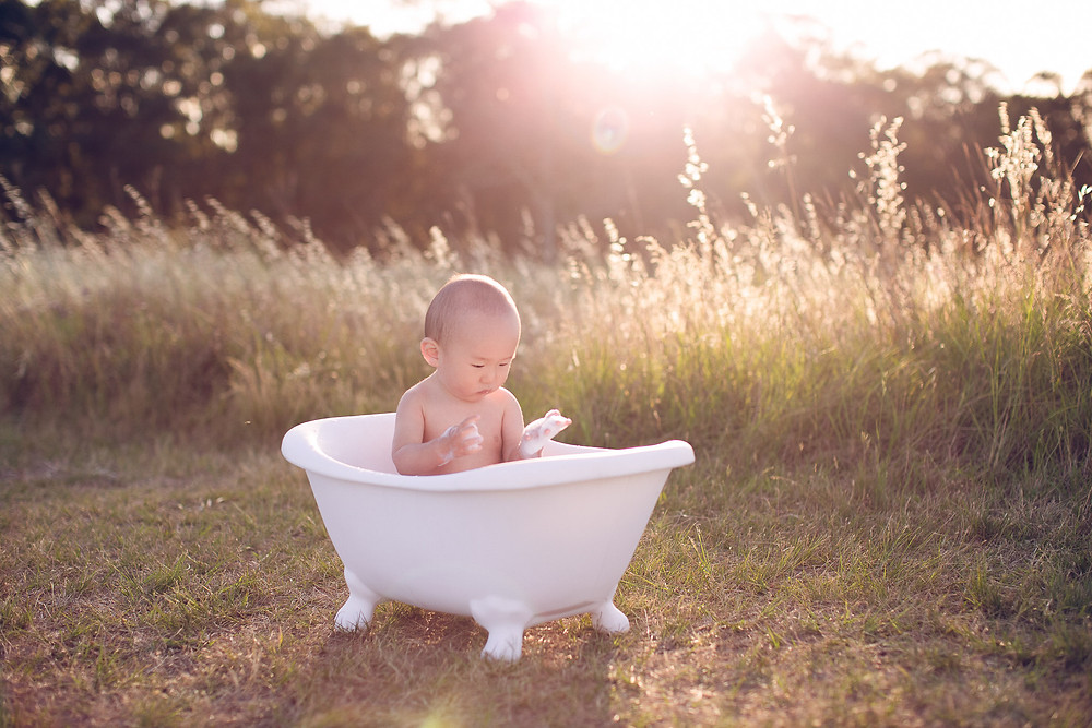 baby enjoying bubbles in bath at golden hour