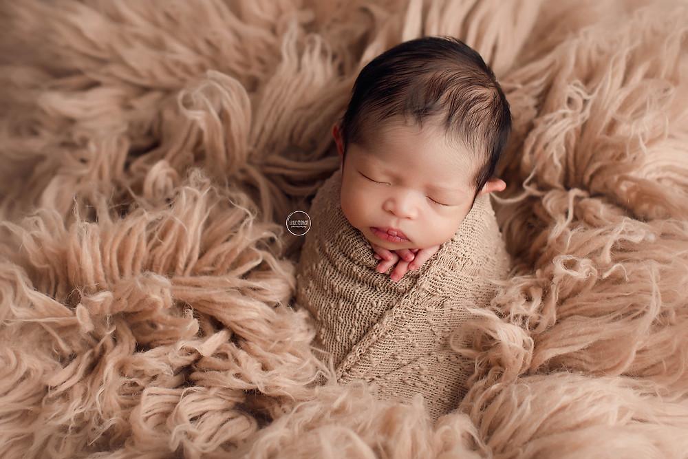 newborn baby in potato sack pose on fur flokati rug