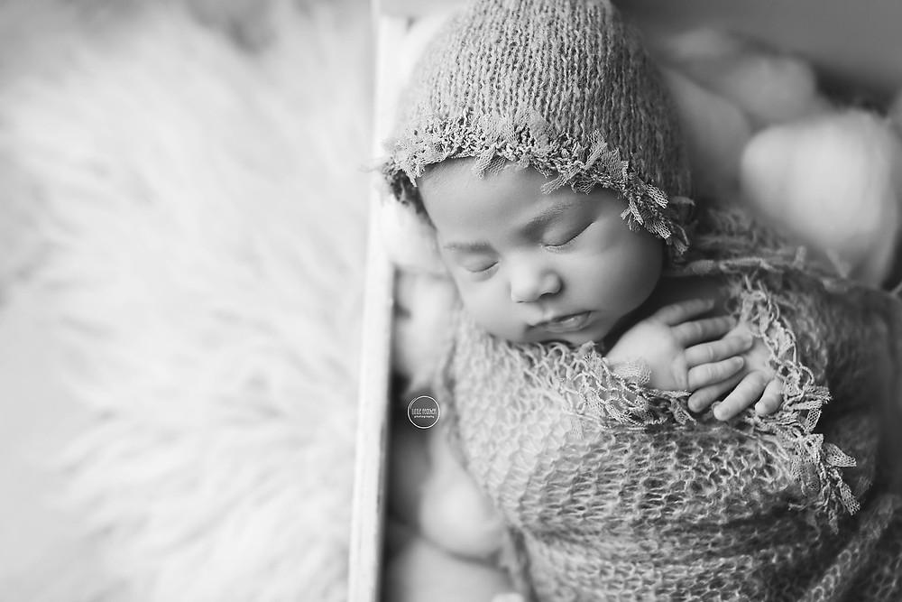 black & white newborn baby girl inside white bed prop
