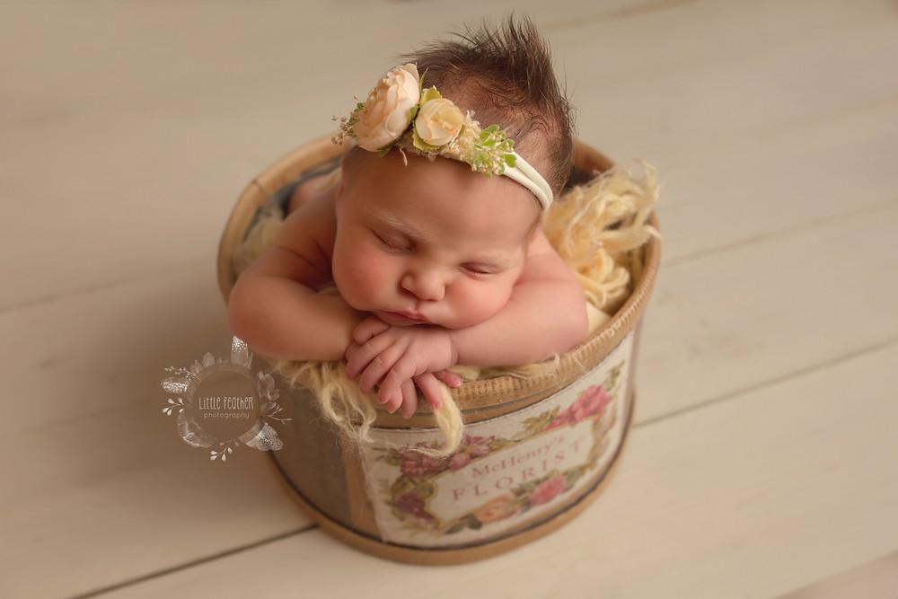 newborn in floral bucket flowers