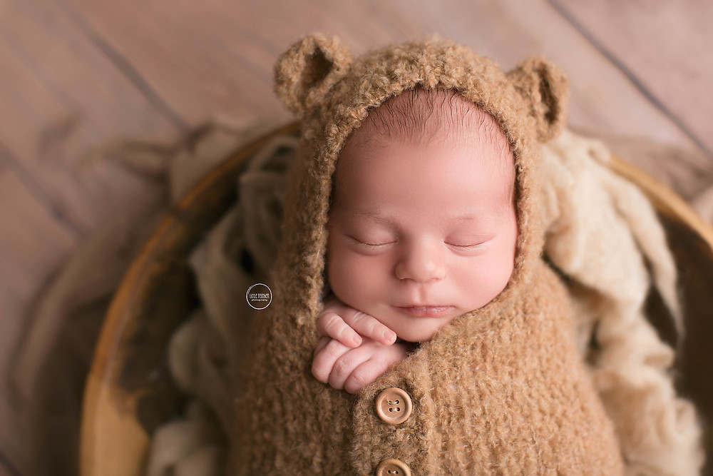 newborn in bear outfit in a bowl of sheets wool tan coloured
