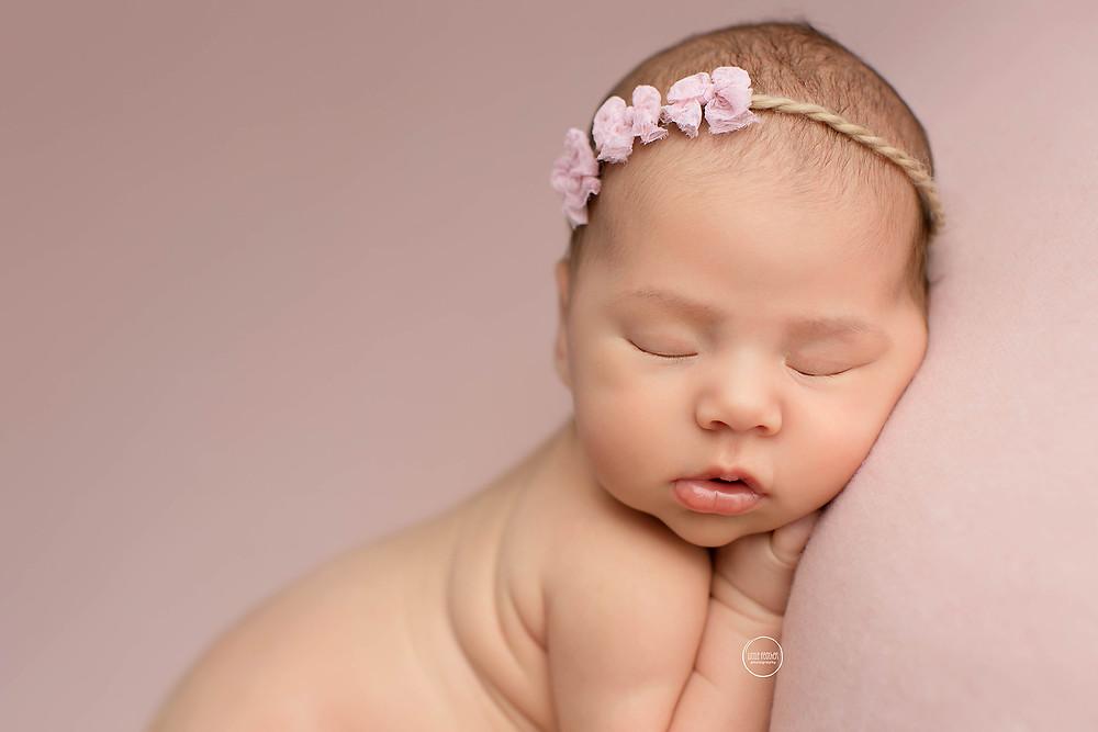 newborn baby girl laying on pink fabric with pink headband