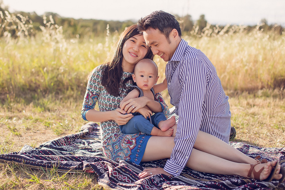 family sitting on rug in field hugging