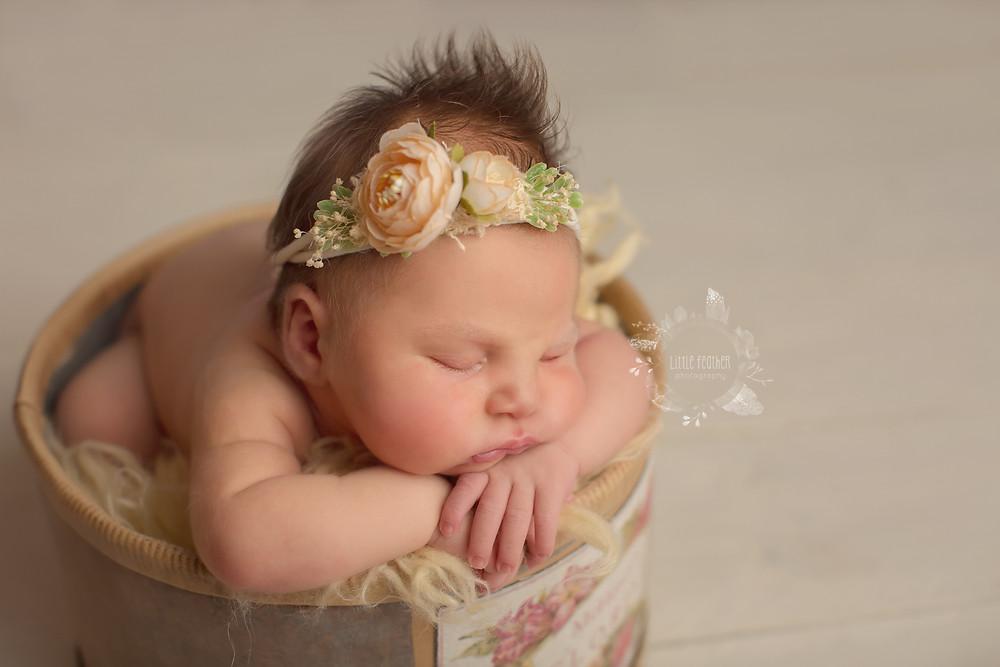 newborn baby in floral bucket