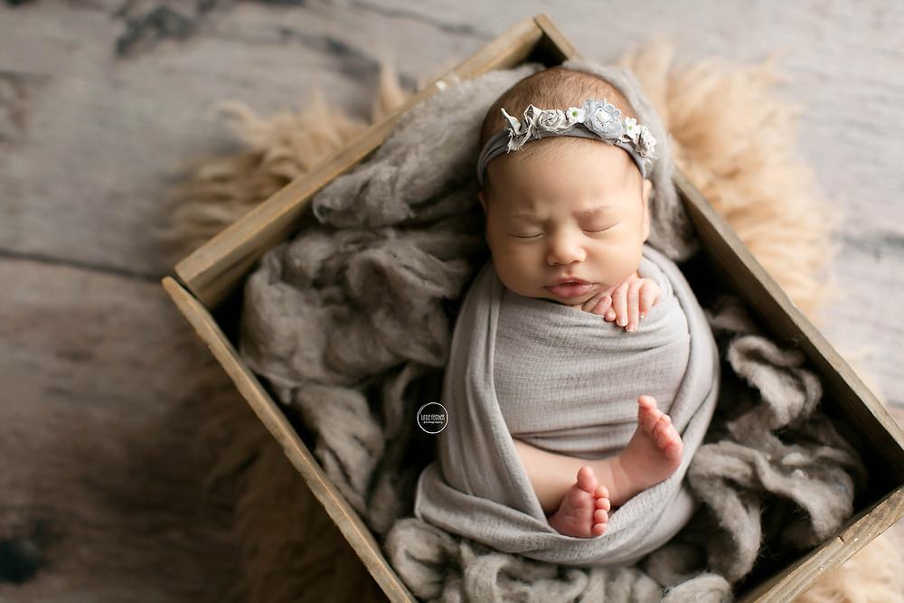 sleeping newborn baby in grey headband and wrap inside a rustic box