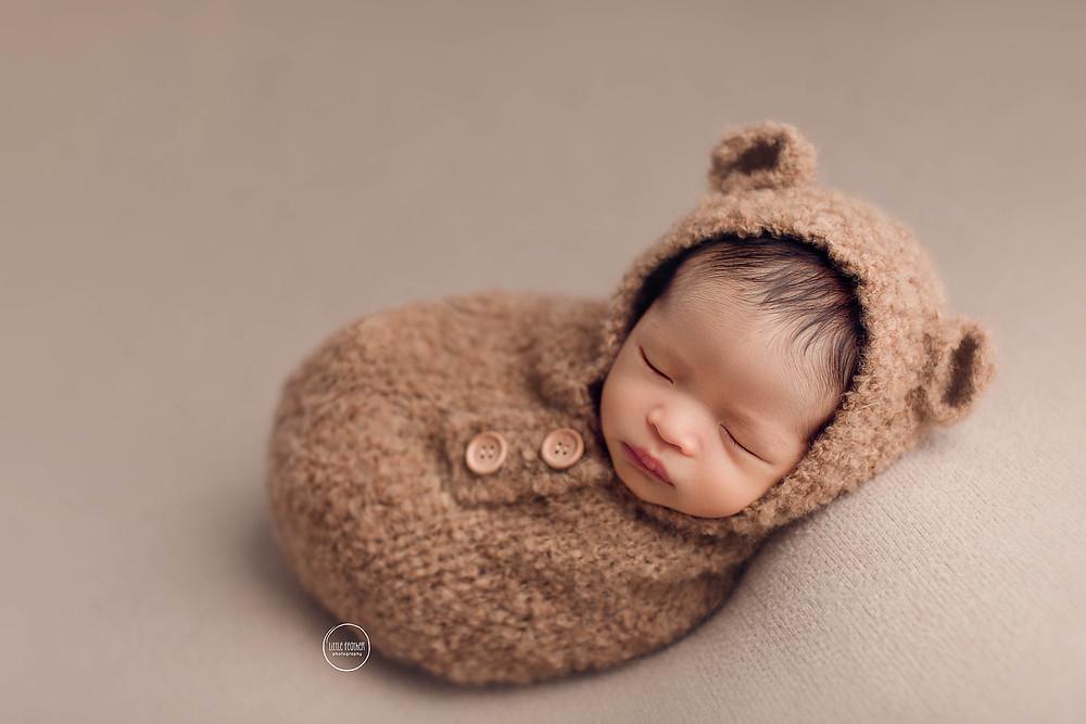newborn boy in teddy bear outfit sleeping on fabric