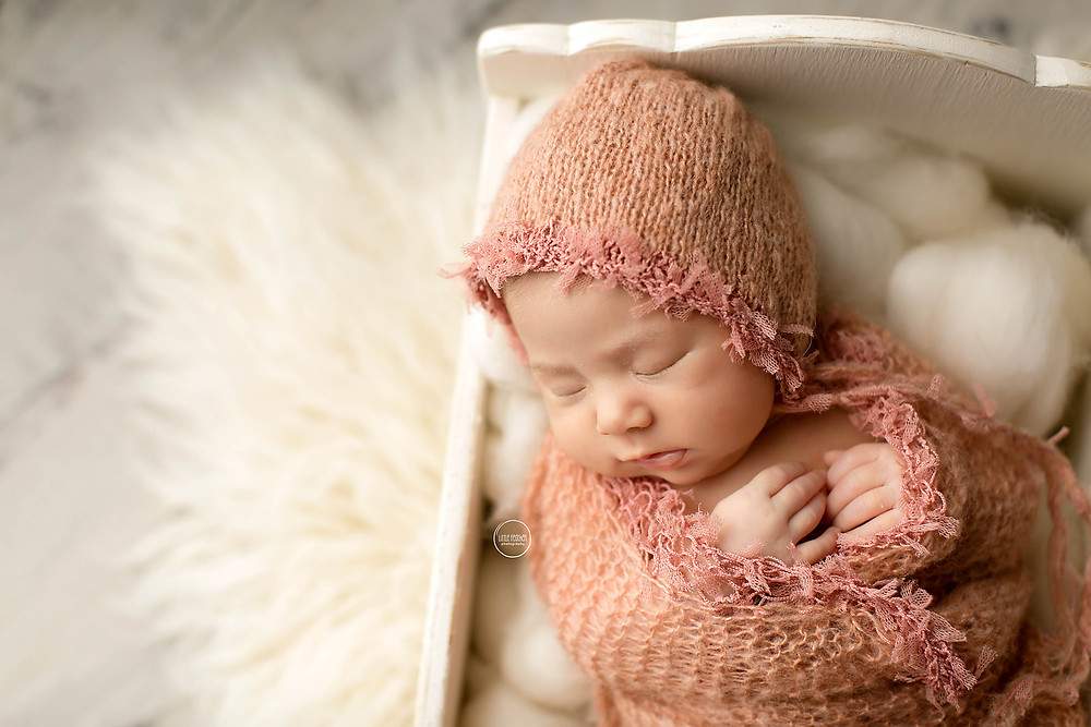 newborn baby girl laying wrapped in peach inside white bed prop
