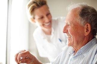 smiling man receiving assistance from nurse
