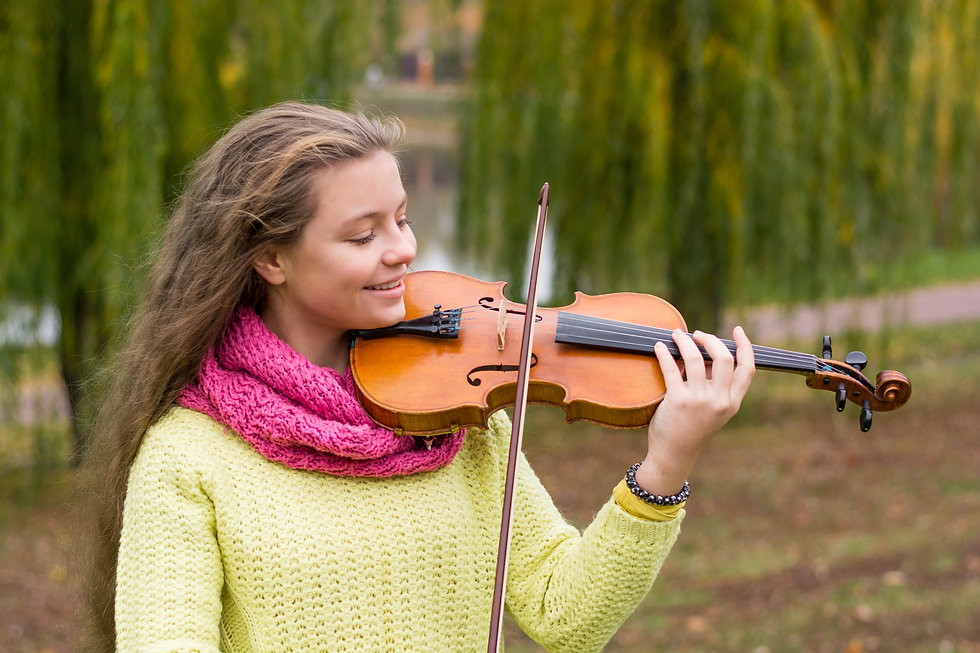 Girl playing the violin in the autumn pa