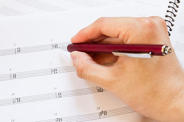 Hand with pen and music sheet, musical b