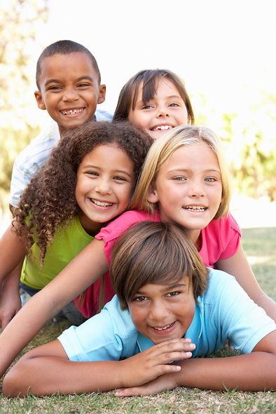 Group Of Children Piled Up In Park.jpg