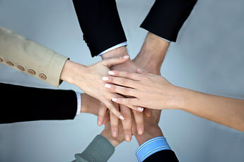 Alt=People's hand's placed over one another in a hand-over-hand huddle