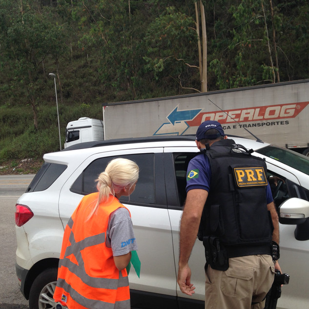Policial Rodoviário Federal acompanha equipe de Gestão Ambiental durante blitz.