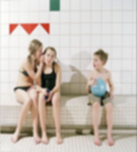 three-kids-sitting-in-a-row-girs-whisper