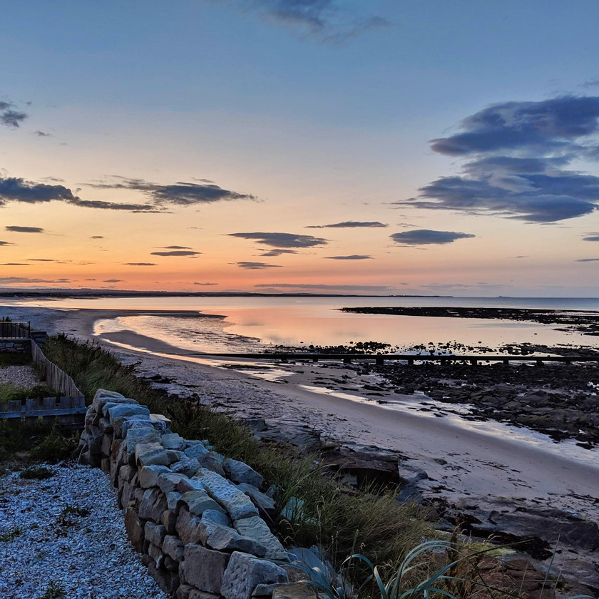 sunset beach Cresswell northumberland UK orange sky blue clouds sand rockpools sea reflection