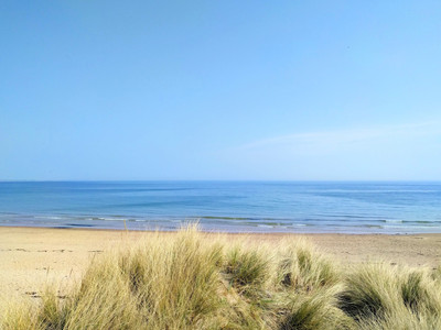 Blue sea on Cresswell beach, Northumberland with sand dunes and white sand