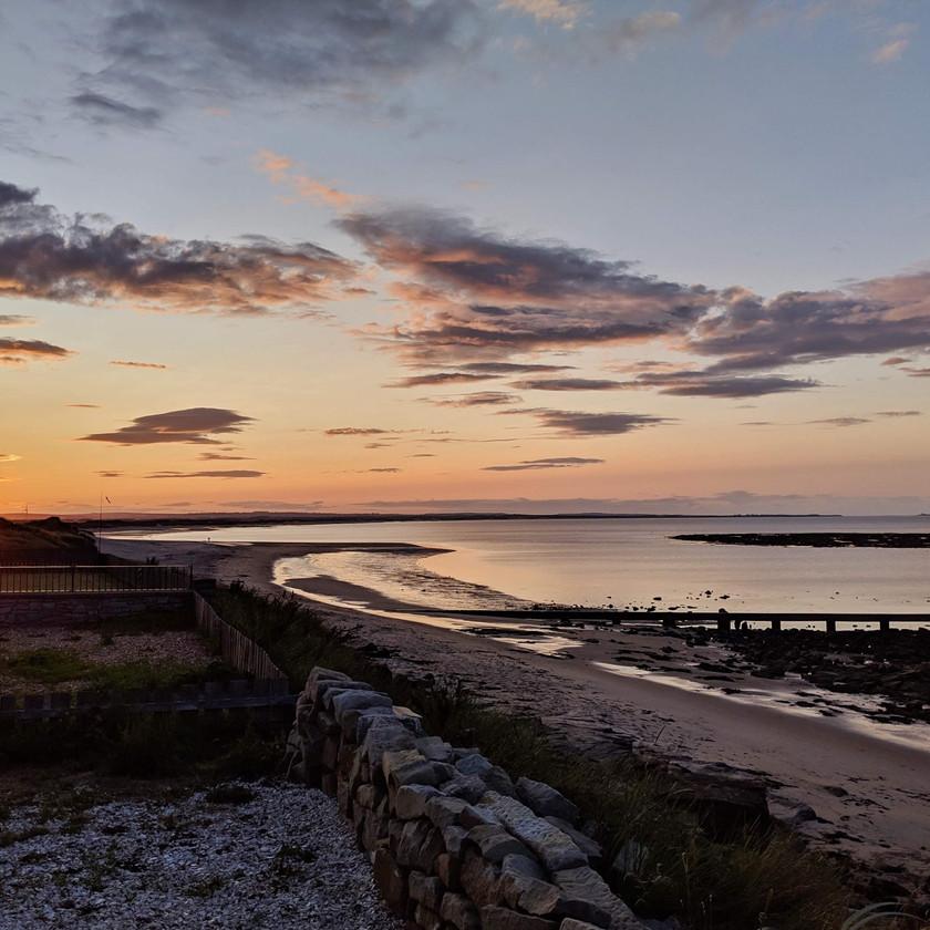 sunset cresswell beach northumberland UK orange sky purple clouds sun rays sea sand pipe rocks horizon