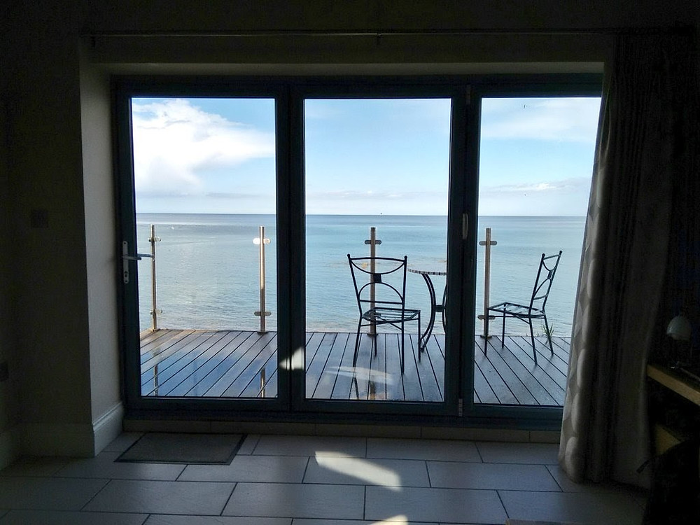 Large window with sea view balcony at Bank top Cottage in Cresswell, Northumberland, UK
