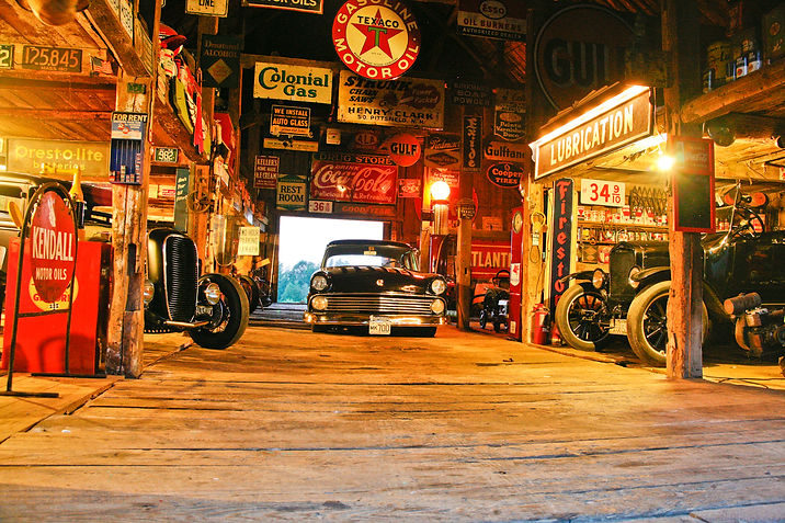 Hot Rods in barn filled with vintage signs