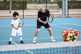 An adult male coach coaching a male youth on an outdoor tennis court