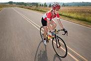 Women on road bike in race gear