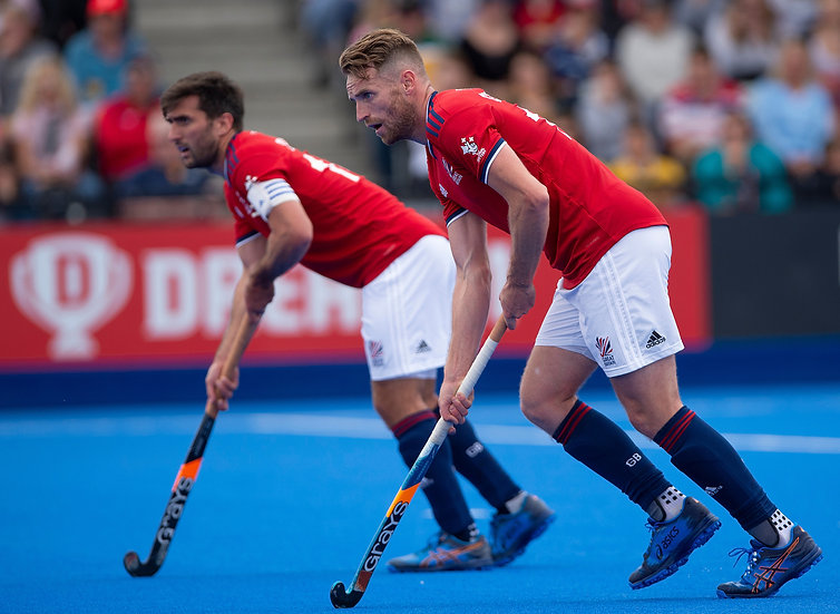 Two men on hockey pitch with sticks