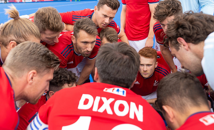 England Men's Hockey team gather in a huddle on hockey pitch