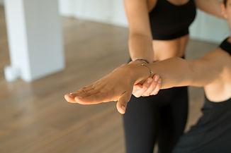 Two girls doing yoga teaching helping close up warm tone.jpg