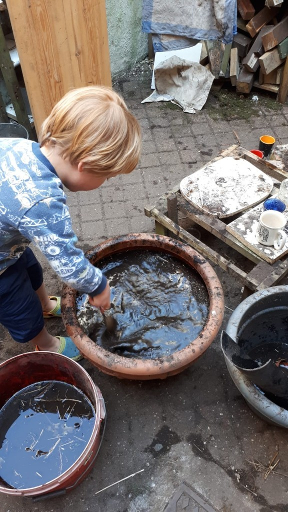 Henry playing in his mud kitchen