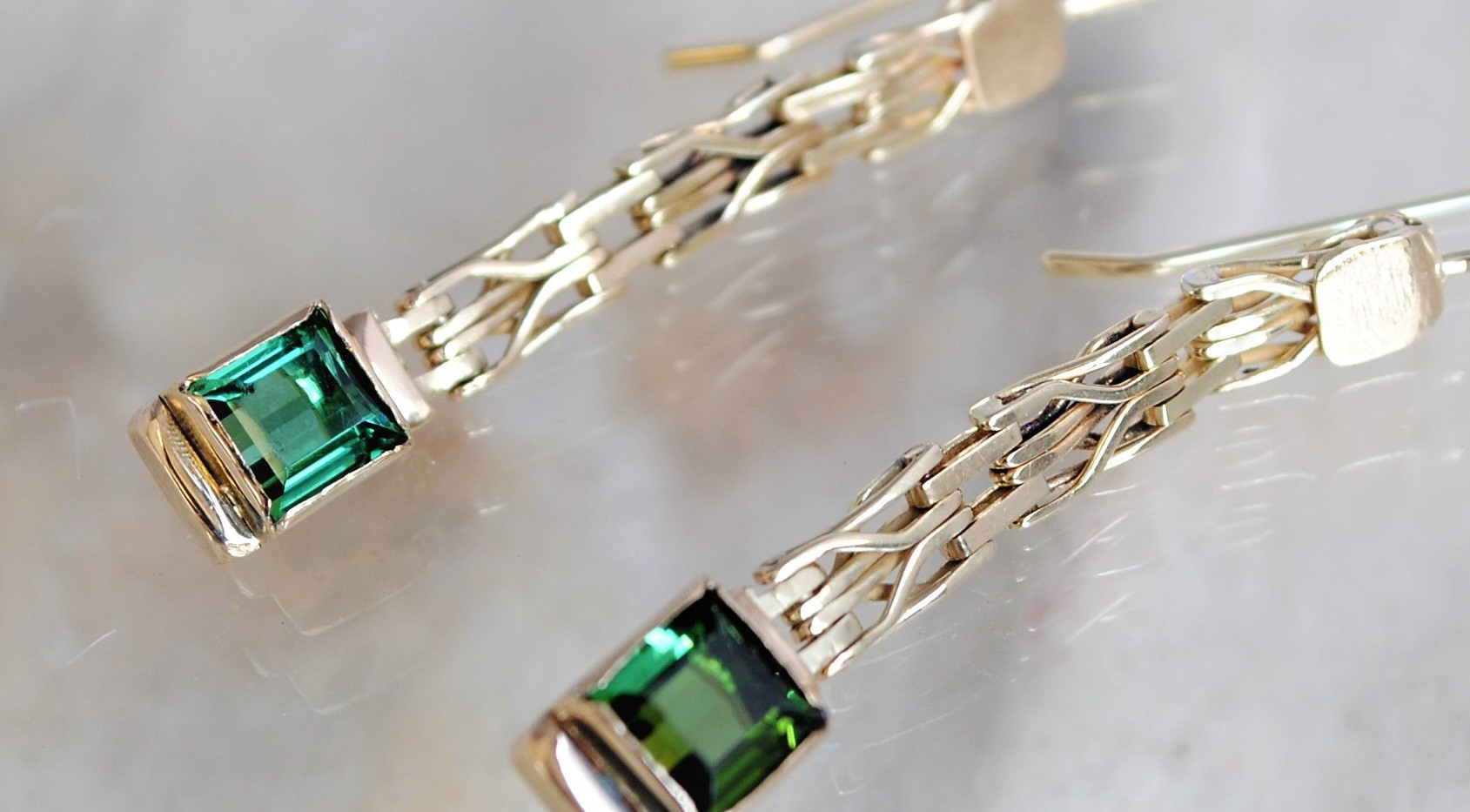 14 carats gold earrings studded with green tourmaline.