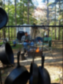 Gary Rivett sitting in front of campfire looking through cast iron cooking utensils wih campe in background at beavercreek state park, ohio