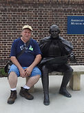 Gary Rivett sittig next to George Washington in Jamestown, VA