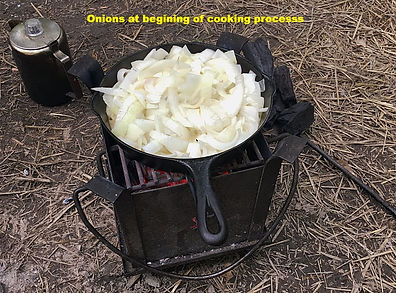 cast iron skillet with chopped onions cookig on a brazier Cast iron stove