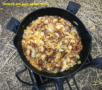 onnions cooking in cast iron skillet on brazier stove