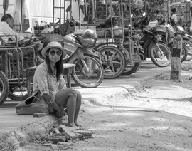 Waif - Poor destitute girl waiting for a lift sitting in the gutter surrounded by motorbikes
