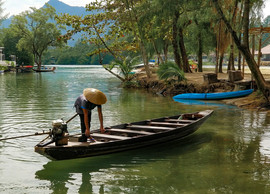 Asian man in boat on tropical river in T