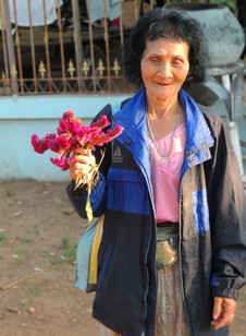 Lady in street holding flowers out