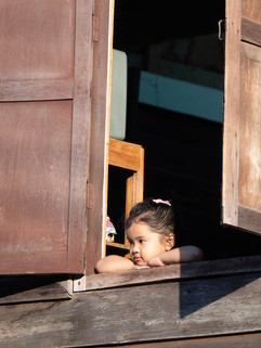 A little girl leaning out of a window dr