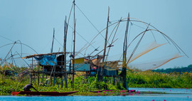 Fishing nets in Asia with man in boat Th